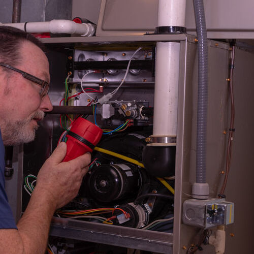 A Technician Examines a Furnace.