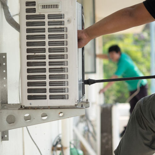A Technician Works on an AC Repair.